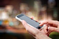 As mãos fêmeas que guardam um telefone celular (smartphone) com tuchscreen na noite imagens de stock royalty free