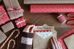 As mãos fêmeas são embaladas pela letra do Natal Imagem de Stock