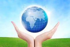 As mãos fêmeas salvar o ambiente mantêm-se no planeta do azul do mundo fotos de stock