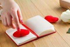 As mãos fêmeas tocam no coração vermelho no diário para o dia de Valentim com g Fotografia de Stock Royalty Free