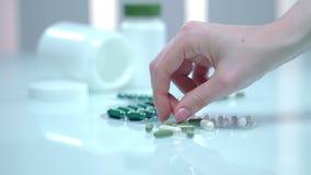 As mãos fêmeas tomam o comprimido verde da tabela Cápsula da medicina alternativa vídeos de arquivo