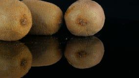 As mãos fêmeas tomam o fruto cortado maduro ao lado do quivi inteiro na superfície do espelho em um fundo preto no estúdio video estoque