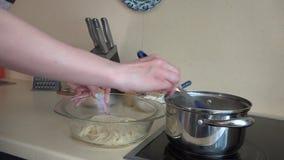 As mãos fêmeas tomam os espaguetes preparados do potenciômetro ao prato de vidro 4K vídeos de arquivo