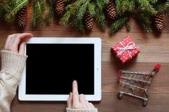 As mãos fêmeas usam a tabuleta na tabela de madeira com objetos do Natal Fotos de Stock
