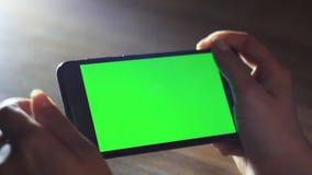 As mãos fêmeas usam um dispositivo móvel com uma tela verde Chave do croma filme