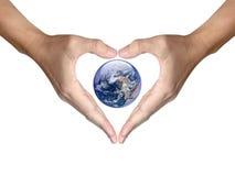 As mãos fazem o coração dar forma à tampa a terra Imagem de Stock