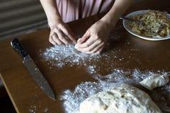 As mãos fecham-se acima da torta da massa do molde para fora Massa e farinha na tabela imagens de stock