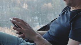 As mãos fecham-se acima Um homem envelhecido médio usa um smartphone Está estudando vários programas Close-up filme