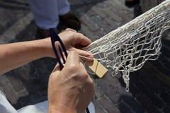 As mãos giram uma rede de pesca Imagens de Stock Royalty Free