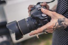 As mãos guardam a câmera de reflexo fotos de stock