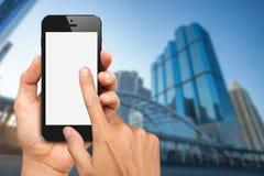 As mãos guardam e tocam no telefone esperto com o escritório que buiding Fotos de Stock Royalty Free