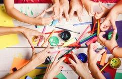 As mãos guardam marcadores, lápis e pinturas coloridos Conceito da arte e do ofício Mãos dos artistas com artigos de papelaria e  foto de stock