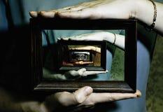 As mãos guardam a moldura para retrato Imagem de Stock