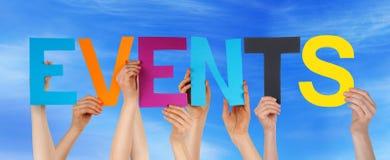 As mãos guardam o céu azul dos eventos retos coloridos da palavra Fotos de Stock Royalty Free