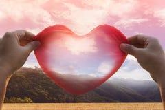 As mãos guardam o coração vermelho grande na opinião romântica da natureza Fotografia de Stock Royalty Free