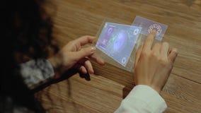 As mãos guardam a tabuleta com trabalho em linha do texto video estoque