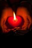 As mãos humanas prendem a vela ardente dada forma coração Fotos de Stock Royalty Free