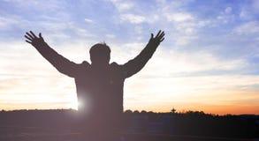 As mãos humildes da elevação do homem da liberdade da silhueta inspiram acima o bom dia Fotografia de Stock
