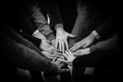 As mãos juntadas de um grupo de pessoas Foto de Stock