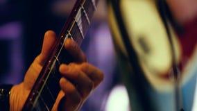 As mãos masculinas apertam o fretboard da guitarra da barra closeup filme