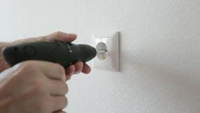 As mãos masculinas com broca de poder desaparafusam a tomada elétrica vídeos de arquivo