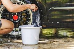 As mãos masculinas com as rodas de limpeza da roda de carro da lavagem da tela da espuma usam a água imagens de stock royalty free