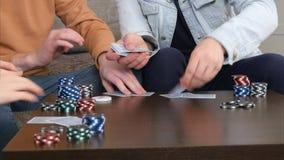 As mãos masculinas dão para fora cartões na tabela na sala de visitas Fotografia de Stock