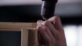 As mãos masculinas do close up usam a chave de fenda eletrônica moderna para conectar pranchas video estoque