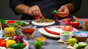 As mãos masculinas do vendedor ambulante nas luvas fazem o taco Petiscos mexicanos da culinária, fast food da cozinha comercial fotografia de stock royalty free