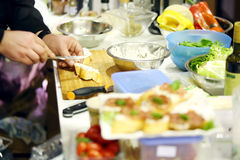 As mãos masculinas dos cozinheiros chefe fazem o sanduíche delicioso na tabela Imagem de Stock