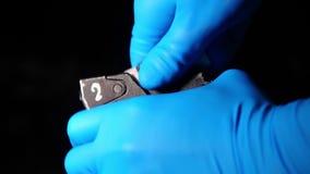 As mãos masculinas em luvas azuis do látex armaram a espingarda automática cartucho super da munição do calibre do magnum de 12 m filme