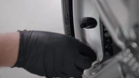 As mãos masculinas em luvas protetoras pretas estão limpando o detalhe do carro pela parte macia de tela, limpando a sujeira, clo vídeos de arquivo