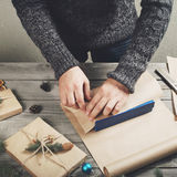 As mãos masculinas envolvem o presente do Natal na tabela de madeira imagem de stock