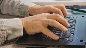 As mãos masculinas estão datilografando no teclado do portátil Close-up O Freelancer trabalha em casa filme