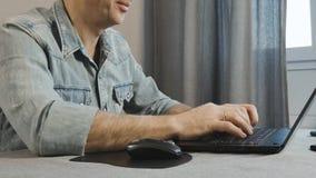 As mãos masculinas estão datilografando no teclado do portátil Close-up O Freelancer trabalha em casa video estoque