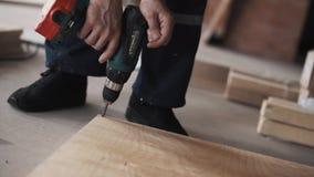 As mãos masculinas estão usando a chave de fenda mecânica para parafusar a prancha de madeira amarela vídeos de arquivo