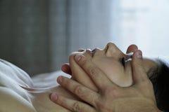 As mãos masculinas fazem uma massagem de cara para a menina Fotografia de Stock