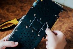 As mãos masculinas guardam uma chave de fenda e um cartão de computação gráfica do reparo imagem de stock