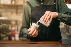 As mãos masculinas preenchem um copo do leite Fotografia de Stock