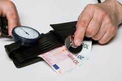 As mãos masculinas puseram um estetoscópio à caixa com euro- dinheiro Fotografia de Stock Royalty Free