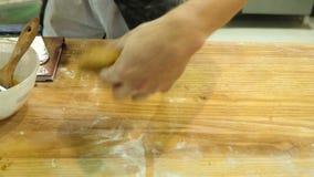 As mãos masculinas que amassam a massa na farinha na tabela e e removem-na vídeos de arquivo