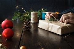 As mãos masculinas que envolvem o fundo rústico do Natal da tabela de madeira da caixa de presente apresentam o fundo fotografia de stock royalty free
