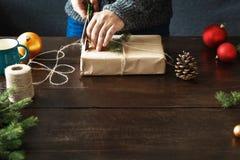As mãos masculinas que envolvem o Natal rústico da tabela de madeira da caixa de presente apresentam o fundo fotografia de stock