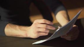 As mãos masculinas que fazem o documento com escrita de alterações nos documentos fecham-se acima Um homem de negócios estuda grá filme