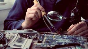 As mãos masculinas que guardam um ferro e a pinça de solda aplicam um fio, o processo de solda sob uma lupa video estoque