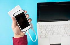 As mãos masculinas que guardam um telefone celular branco conectaram a um banco do poder fotografia de stock