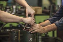 As mãos masculinas que trabalham a rotação parte em uma fábrica velha para instalar fotografia de stock