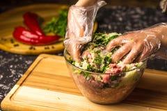 As mãos misturam a carne de porco triturada crua em uma bacia de vidro imagem de stock royalty free