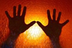 As mãos mostram em silhueta no fundo alaranjado da cor do fogo Imagens de Stock Royalty Free