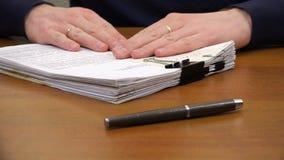 As mãos movem uma pilha de documentos para a pena na tabela video estoque